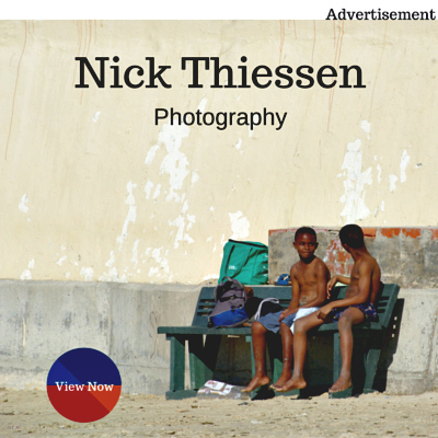 Nick Thiessen photograph of two young black South African boys sitting on a bench against a beige wall.